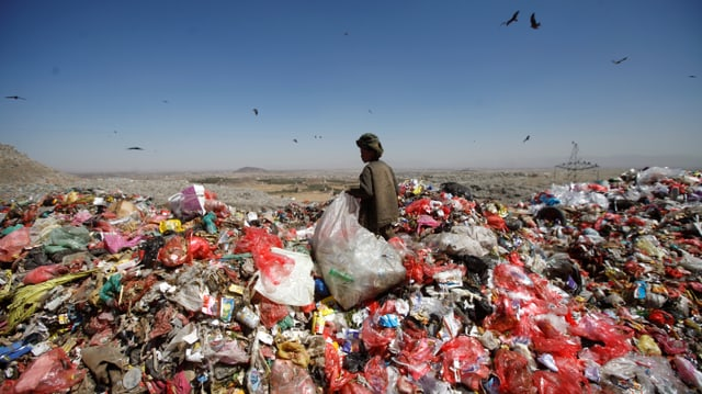 Müllberg mit Kind, das sammelt