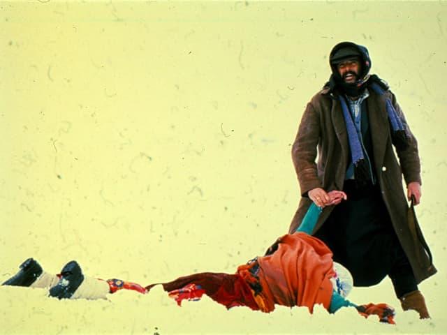 Filmstill: Ein Mann hebt den Arm eines leblos am Boden liegenden Menschen.
