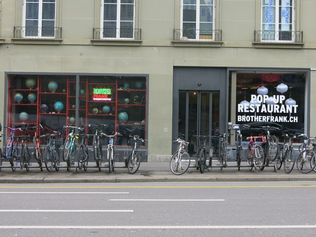 """Fahrräder stehen vor dem Schaufenster des vietnamesischen Streetfood Restaurant """"Brother Frank"""" im Berner Bollwerk"""