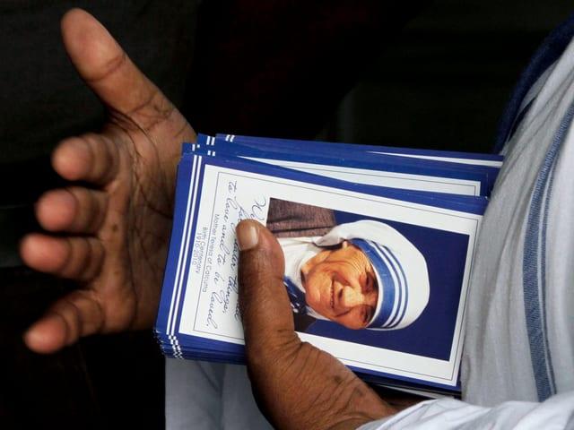 Eine Hand hält Karten mit dem Bild Mutter Teresas.