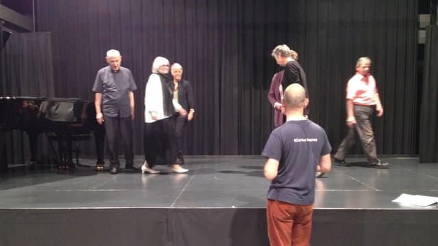 Auf der schwarzen Bühne stehen und gehen ein paar ältere Menschen. Im vordergrund der Regisseur.