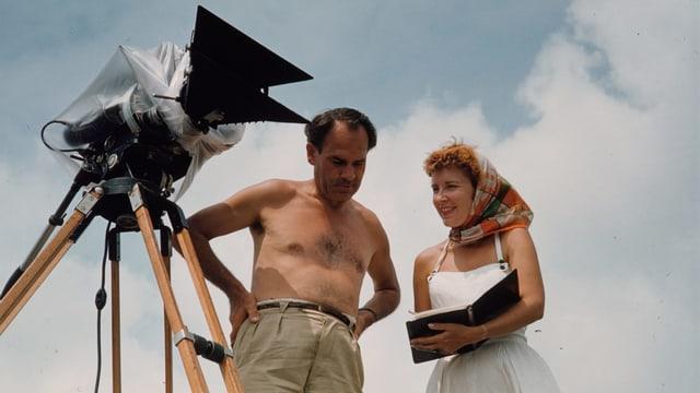 ein Mann mit nacktem Oberkörper bespricht sich mit einer Frau mit Schal