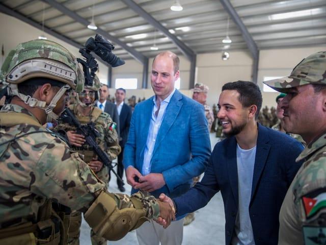 Prinz William trägt ein blaues Jackett. Neben ihm stehen Männer in Tarnanzügen.