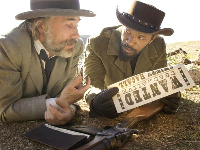 Filmszene: Christoph Waltz und Jamie Foxx liegen nebeneinander in der Wüste und schauen auf ein Wanted-Plakat.