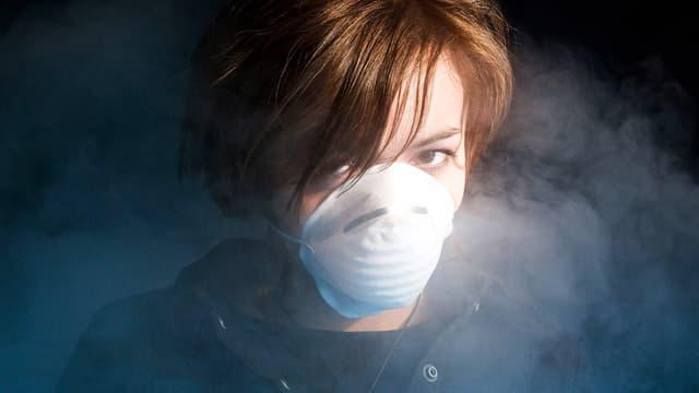 Frau mit medizinischer Schutzmaske in Rauchwschwaden