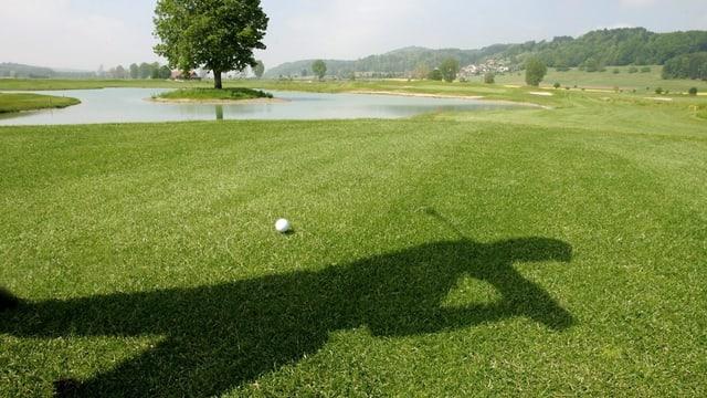 Ein Schatten eines Golfers, ein Golfball auf dem Rasen.