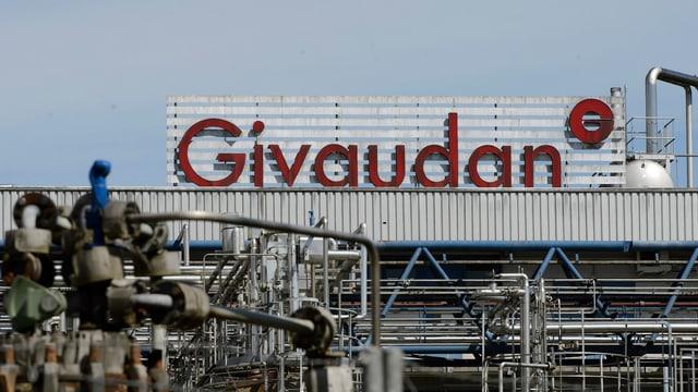 """Blick auf das Firmengelände in Vernier bei  Genf mit Röhren im Vordergrund und dem Schriftzug """"Givaudan"""" auf einem Firmengebäude."""