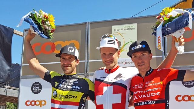 Alban Lakata, Urs Huber e Jochen Käss stattan en posa da victurs (podest 2,1,3) avant ina paraid da sponsors. tuts tegnan in matg flurs en l'aria.