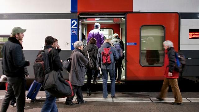 Menschen steigen in einen Zug ein.