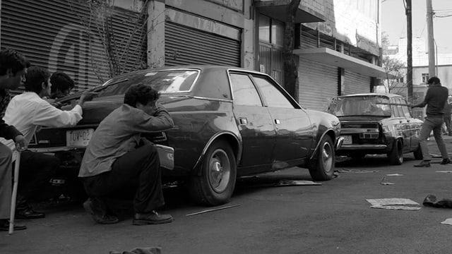 Männer verstecken sich hinter einem geparkten Auto.