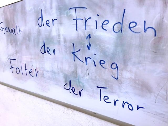 Wandtafel mit den Begriffen Frieden, Krieg, Folter und Terror.