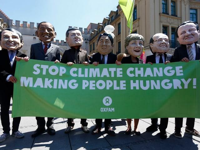 7 Protestierende, die übergrosse Masken von Politiker an haben.