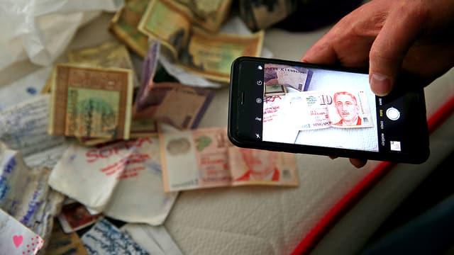 Eine Männerhand mit einem Handy. Er macht eine Aufnahme von einem Bett mit Geld darauf.