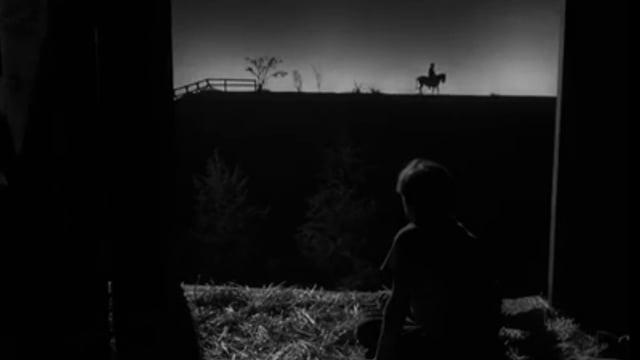 Mann reitet in der Ferne auf einem Pferd
