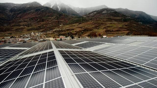 Solarzellen, im Hintergrund ein Dorf und Hügel.