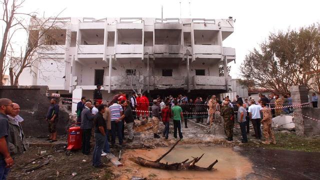 Im Hintergrund die stark beschädigte französische Botschaft, im Vordergrund Schaulustige