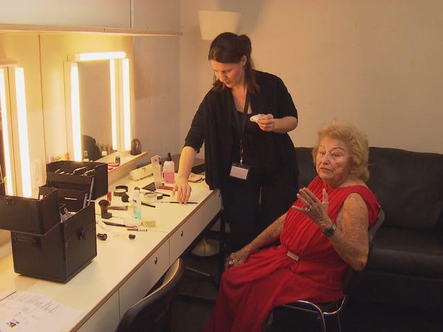 Eine ältere Frau sitzt vor einem grossen Spiegel und lässt sich schminken.