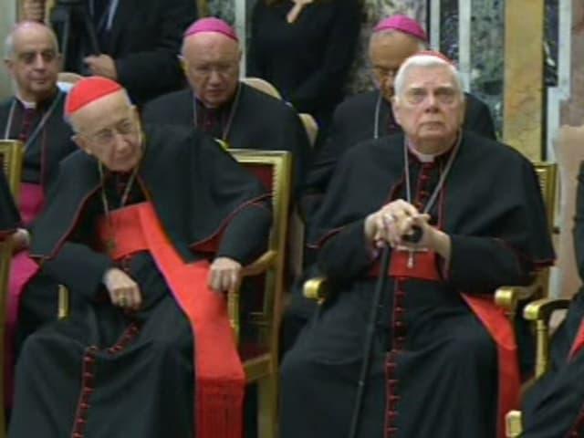 Ältere Bischöfe sitzen auf ihren Stühlen.