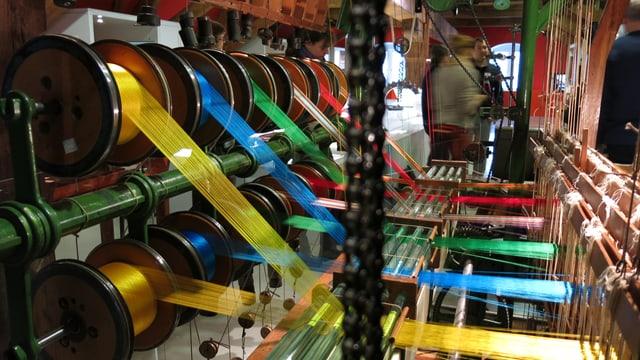 Blick auf- und in einene Webstuhl für Seidenbänder mit bunten aufgespannten Fäden.