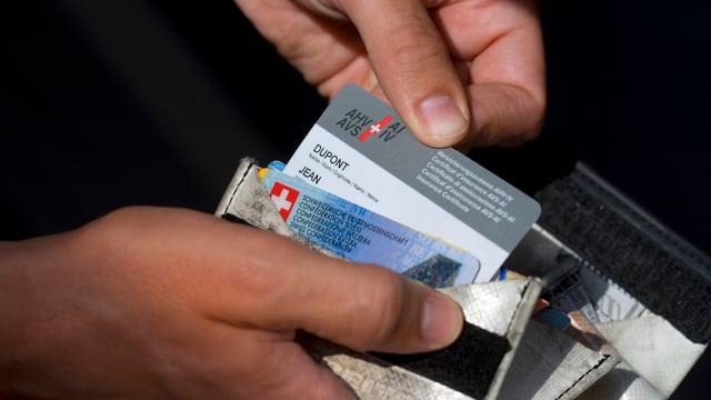 Zwei Hände halten ein Portemonnaie und ziehen einen AHV-Ausweis raus.