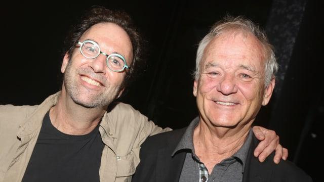 Zwei Männer schauen lachend in die Kamera.