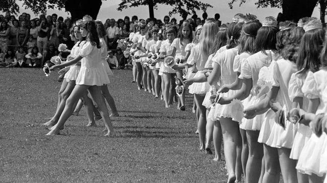 Mädchen in weissen Kleidchen tanzen einen Reigen.