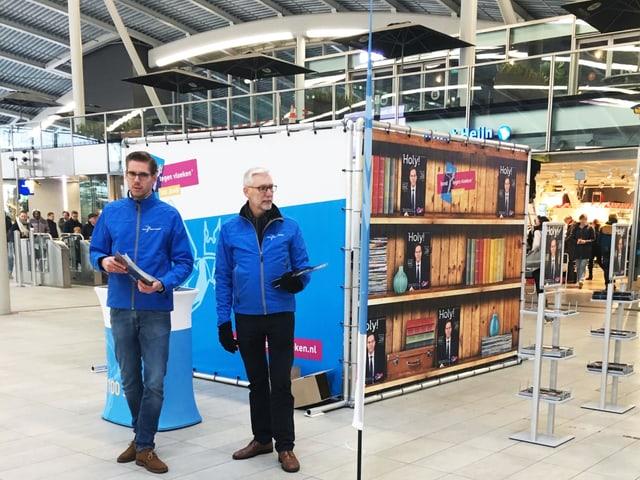Zwei Männder in gleicher Jacke stehen an einem Stand in einer Halle.