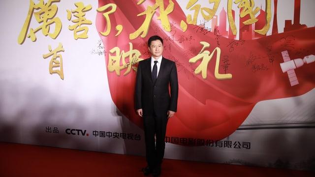 Der chinesische Schauspieler Wu Jing steht vor einem Plakat des Dokumentarfilms «Amazing China».