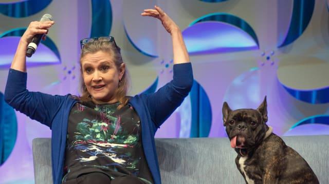 Carrie Fisher hebt ihre Arme, neben ihr: Ihr Hund Gary.