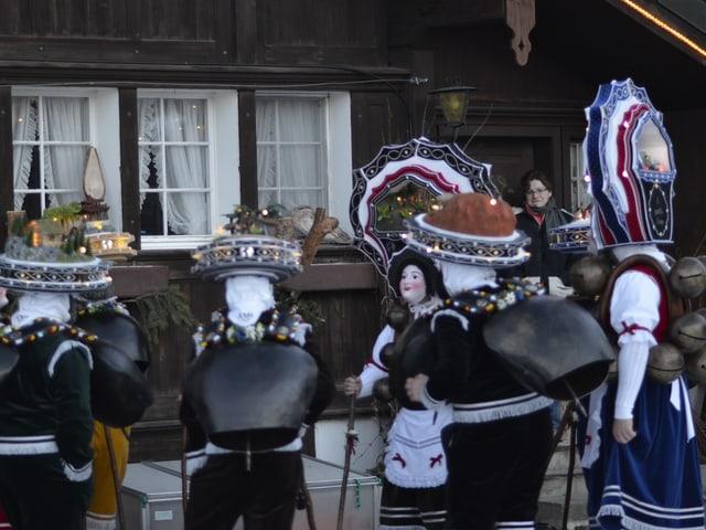 Gruppe an Silvester-Chläusen singt vor Haus im Winter.