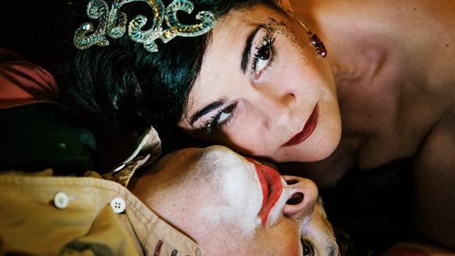 Stark geschminkte Frau mit Paietten im Haar lehnt sich über toten Clown.