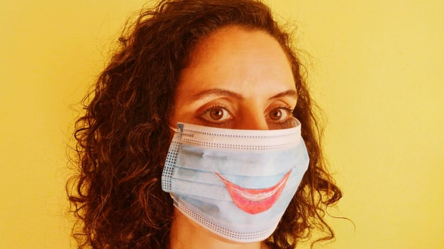 Eine Frau trägt einen Mundschutz. Auf diesem ist ein lachender Mund gezeichnet.