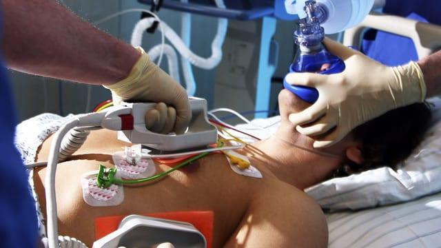 Patient mit Herzkreislaufstillstand wird notfallmässig beatmet, während der Einsatz eines Defibrillators vorbereitet wird.