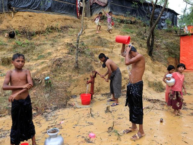Kinder waschen sich im Flüchtlingslager im Freien.