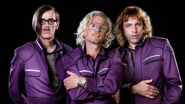 Drei Männer mit langen Haaren in violetten Anzügen