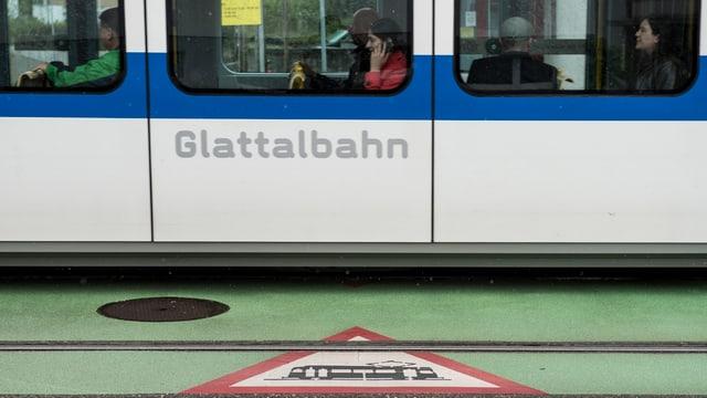 Ein Tram, darauf steht Glattalbahn, die Strasse davor grün mit Achtung Tram Schild.