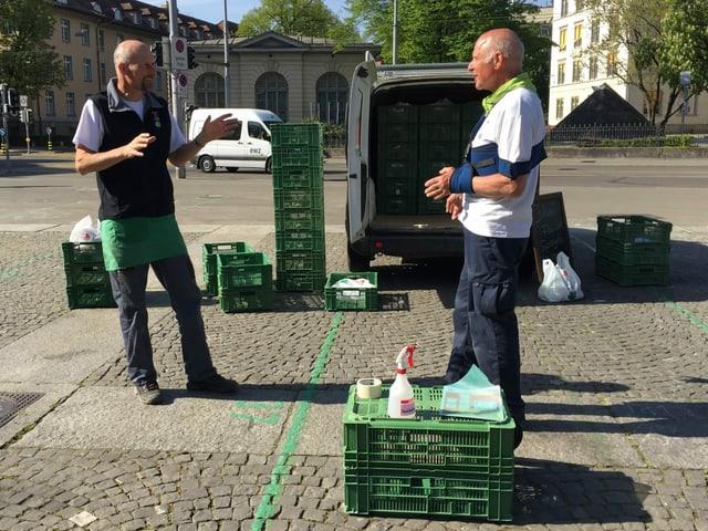 Zwei Mitglieder des Familienbetriebs Haab Walser stehen vor ihren ausgeladenen Gemüsekisten auf einem Platz in der Stadt Zürich.