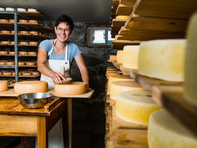 Theresia Hollenstein steht hinter einem Tisch mit Käse, um sie herum sind Regale mit weiteren Käseleibern zu sehen.