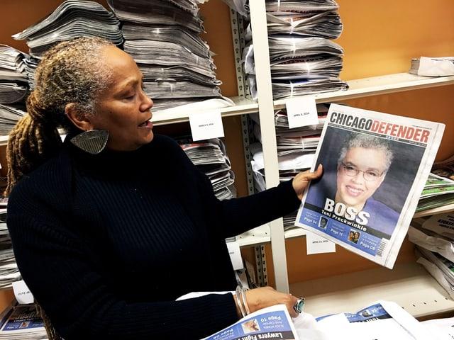 Chefredaktorin Kai El'Zabar hält eine Ausgabe der Wochenzeitung in der Hand.