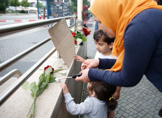 Trauernde Familie zündet Kerzen an