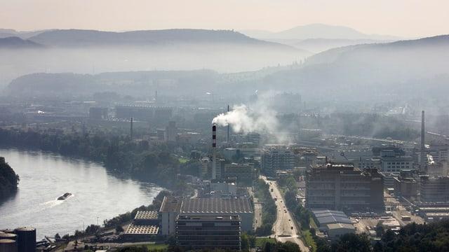 Industrieareal mit rauchenden Kaminen, dahinter Jurahügel im Dunst.