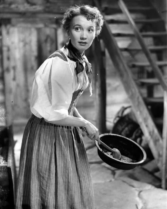 Eine junge Frau blickt an uns vorbei, in der Hand hält sie eine Holzschüssel und Rührkelle.