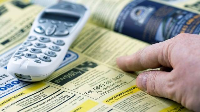 Ein offenes Telefonbuch: ein Finger zeigt auf ein gelbes Inserat darin. Daneben liegt ein weisses Telefon.