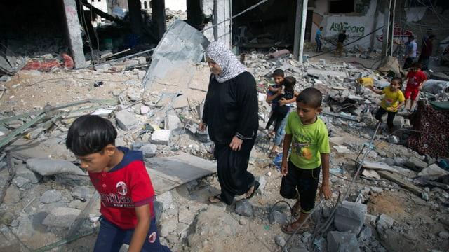 Eine Frau und mehrere Kinder laufen durch eine komplett zerstörte Wohngegend.