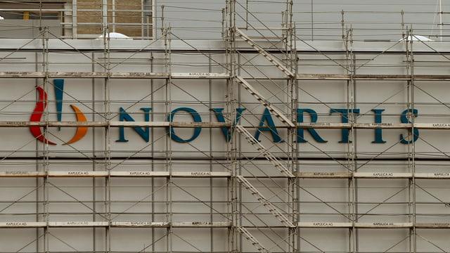 Novartis-Logo an einer Hauswand, davor ein Baugerüst