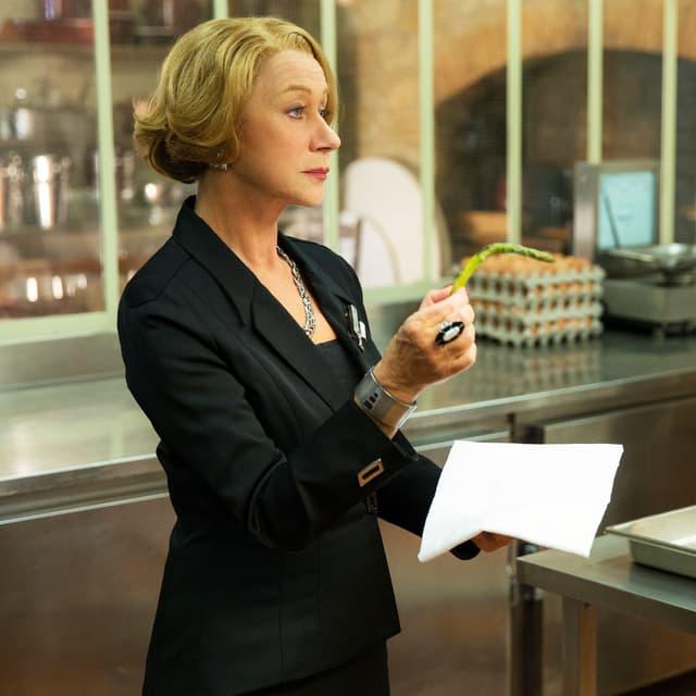 Helen Mirren als Madame Mallory, französische Restaurant-Chefin mit einer geknickten Spargel in der Hand in der Küche.
