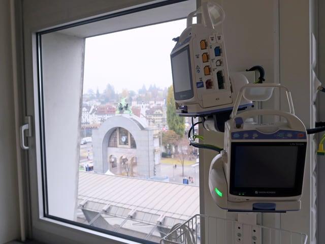Ein Überwachungsgerät in einem Aufwachraum; daneben ein Fenster mit Blick auf den Torbogen vor dem Luzerner Bahnhof.