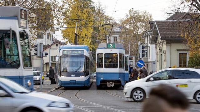 Zürcher Heimplatz mit zwei Trams, die sich kreuzen.