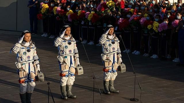 Drei Astronauten salutieren neben einer Menschenmenge.