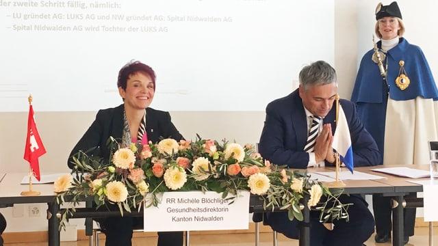 An einer Medienkonferenz sitzen eine Frau und ein Mann an einem Tisch, davor ein Blumenbouquet.